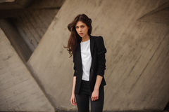 Young brunet woman standing outside in black jacket, jeans wearing hills . horizontal Royalty Free Stock Photo