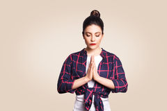 Young brunete woman practising yoga, holding hands in namaste and keeping her eyes closed. Caucasian girl meditating. Indoors, praying for peace and love Royalty Free Stock Photos