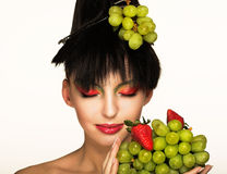 Young brunette. Portrait of pretty brunette with strawberry and green grapes Stock Image