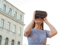Young brunette is amused by her first encounter with futurist virtual reality glasses Stock Images