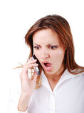 Young brunette with angry expression on face speak. The Young brunette with angry expression on face speakin on cell phone Royalty Free Stock Images