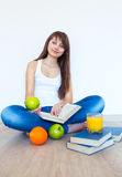 Young brunette with apple reading a book at home Stock Photo