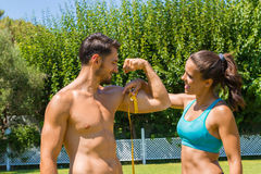 Young brunette athlete measures the biceps of Stock Image