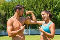 Young brunette athlete measures the biceps of Royalty Free Stock Photography