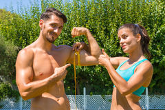 Young brunette athlete measures the biceps of Stock Photography