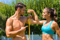 Young brunette athlete measures the biceps of Royalty Free Stock Photo