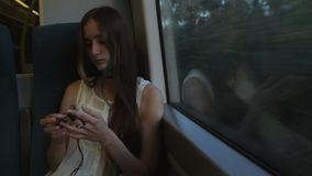 Young brunette beautiful hipster girl with long hair unravels the headphones, sitting by the window in the train. In the evening stock video footage