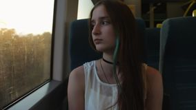Young brunette beautiful hipster girl with long hair yawns, sitting by the window in the train. In the evening stock video