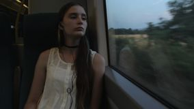 Young brunette beautiful hipster girl with long thinking about her life, sitting by the window in the train. In the evening stock video