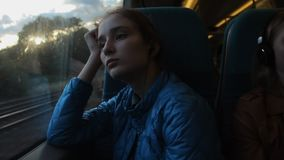 Young brunette beautiful hipster girl looking to the window in the train and thinking about her future. Evening stock footage