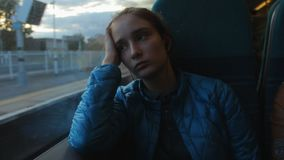 Young brunette beautiful hipster girl looking to the window in the train and thinking about her future. She is. Thoughtful. Evening stock video