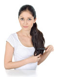 Young brunette beautiful lady combing hairs Royalty Free Stock Photos