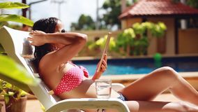 Young brunette beautiful woman wearing sunglasses and bikini drinks water using tablet lying on sunbed by pool stock footage