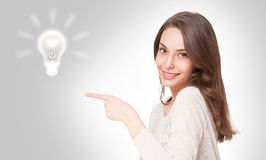 Young brunette beauty with light bulb symbol. Royalty Free Stock Images