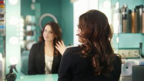 Young brunette in a beauty salon admiring her reflection in the mirror stock footage