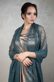 Young brunette in a beige silk dress and green lace capes standing on gray background. Vertical photo Stock Photos