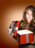 Young brunette with big red gift box. Beautiful young brunette opening big red gift box with light streaming out Royalty Free Stock Images