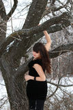A young brunette in a black dress in the forest Stock Photo
