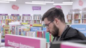 Young brunette black-haired man with glasses looking books on the bookshelves in the bookstore. Young brunette black-haired man with glasses looking books on stock video