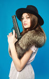 A young brunette in a black hat with a gun in his hand Stock Photos