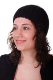 Young Brunette in Black Knit Cap Smiling to Side. A young brunette woman in a black knit cap looking to the side smiling Royalty Free Stock Photo