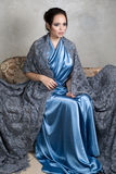 Young brunette in a blue silk dress and lace long Cape sits on a vintage sofa. Vertical photo Royalty Free Stock Photography