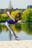 Young brunette in a blue sports shirt doing a jump on the beach. Woman doing fitness exercise outdoors. Stock Image