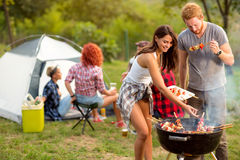 Young brunette with boyfriend serving on plate barbecue Royalty Free Stock Image