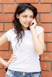 Young brunette at brick wall talking cellphone Stock Images