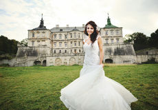 Young brunette  bride against castle in west Ukraine Stock Photo