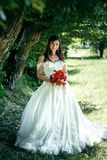 Young brunette bride with beautiful smile is holding the red wedding bouquet. Park location. Vertical full-length shot. Young brunette bride with beautiful Stock Images