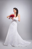 A young brunette bride holding flowers Royalty Free Stock Images