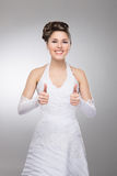 A young brunette bride holding thumbs up Royalty Free Stock Images