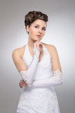 A young brunette bride posing in a white dress Royalty Free Stock Images
