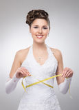 A young brunette bride posing in a white dress with a tape. A young and happy brunette Caucasian bride posing in a white dress and holding a measuring tape. The Royalty Free Stock Images