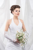 A young brunette bride in white clothes holding flowers Royalty Free Stock Photo
