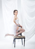 A young brunette bride in white erotic clothes Stock Photography