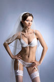 A young brunette bride in white erotic lingerie Stock Photos