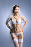 A young brunette bride in white erotic lingerie Stock Photo