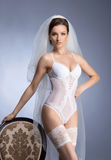 A young brunette bride in white erotic lingerie Royalty Free Stock Image