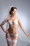 A young brunette bride in white erotic lingerie Stock Photography
