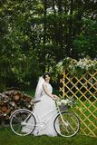Young brunette bride in white fashionable dress with bicycle and with a bouquet of flowers in the summer garden stock images