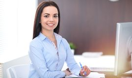 Young brunette business woman looks like a student girl working in office. Hispanic or latin american girl happy at work. And too busy stock images