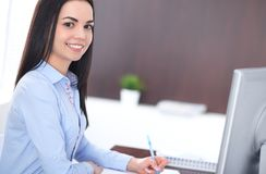 Young brunette business woman looks like a student girl working in office. Hispanic or latin american girl happy at work royalty free stock photos