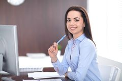 Young brunette business woman looks like a student girl working in office. Hispanic or latin american girl happy at work stock photos