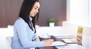 Young brunette business woman looks like a student girl working in office. Hispanic or latin american girl happy at work royalty free stock photo