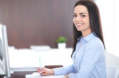 Young brunette business woman looks like a student girl working in office. Hispanic or latin american girl happy at work stock photo
