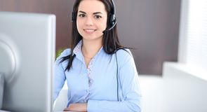 Young brunette business woman looks like a student girl working in office. Hispanic or latin american girl talking by royalty free stock photo