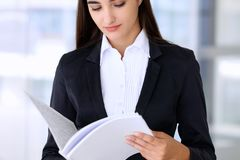 Young brunette business woman or student girl looking into note book Stock Image