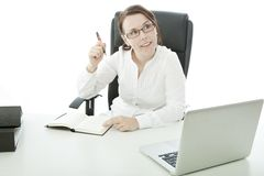 Young brunette businesswoman on desk has an idea Stock Photography